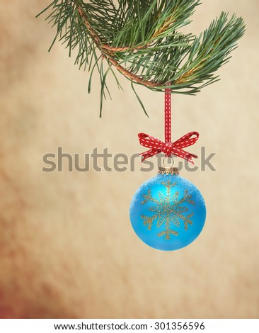 Traditional Christmas Tree Decoration hanging from a tree branch on a textured background. - stock photo