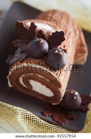 Traditional Christmas Yule Log cake decorated with chocolate chestnuts, selective focus - stock photo
