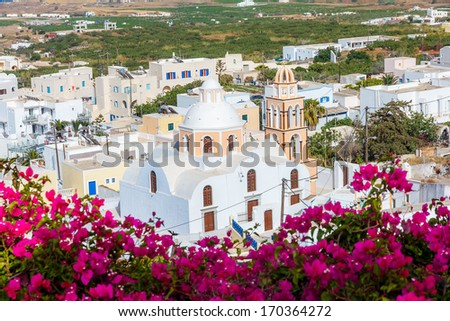 Traditional church at Fira, Santorini in Greece with flowers in front - stock photo