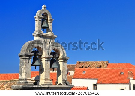 Traditional church tower with three bells profiled on blue sky, Dubrovnik, Croatia - stock photo
