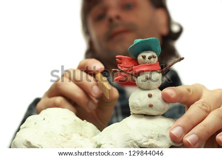 traditional clay animator at work on snowman miniature - stock photo
