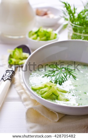 Traditional cold soup of cucumber on a wooden background. Selective focus.