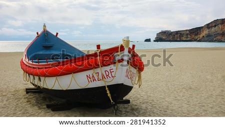 Traditional colorful  boat on the beach of Nazare (Portugal) at evening dusk. - stock photo