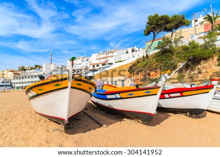 Traditional colourful fishing boats on beach in Carvoeiro village, Algarve region, Portugal - stock photo