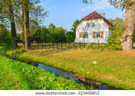 Traditional cottage house and small river in countryside landscape, Radziejowice village, Poland - stock photo