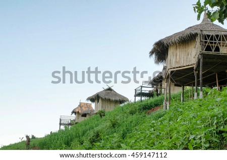 Traditional cottage in the village of Akha tribe atop the mountain, Thailand, Sunset. - stock photo