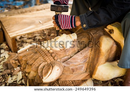 Traditional craftsman carving wood - stock photo