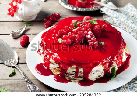 Traditional crepe cake with custard cream and fresh berry topping on a wooden background - stock photo