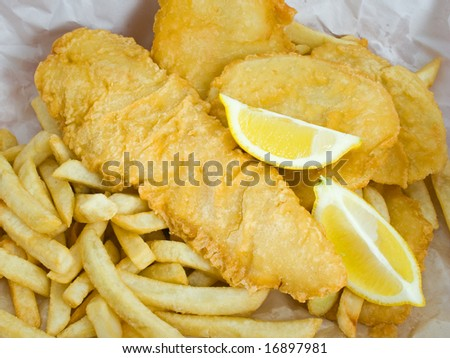 Traditional deep fried fish and chips with lemon in paper wrapping - stock photo