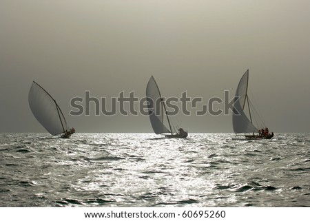 Traditional dhows sailing in the Arabian Gulf near Dubai. - stock photo