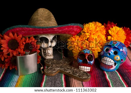 Traditional Dia De Los Muertos (Day of the Dead) altar/offering. With marigold & red sunflowers, colorful lumineras, decorative cross, tequila flask, & skull wearing Mexican sombreo. - stock photo