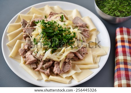 Traditional dish of Turkic people in Central Asia Beshbarmak. Focus on the greens - stock photo
