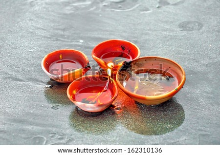 Traditional Diwali lamps and candles lit on the sand beach. Selective focus, shallow DOF and visible noise due to low light. - stock photo
