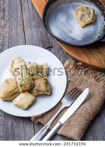 traditional dumplings with sauerkraut and mushrooms on old wooden table - stock photo