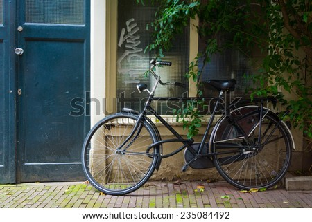 Traditional dutch bicycle parked at the front door in Amsterdam - stock photo