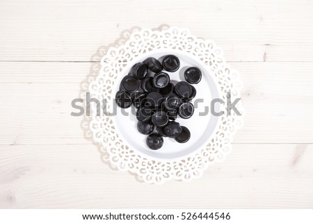 Traditional Dutch candy drop on little plate on wooden background