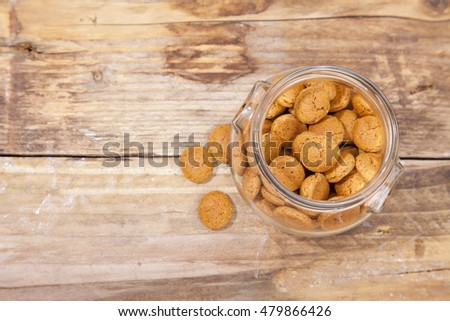 Traditional Dutch candy pepernoot in glass jar on wooden background