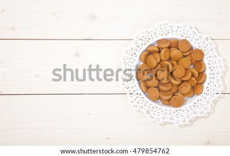 Traditional Dutch candy pepernoot on white plate on white wooden background