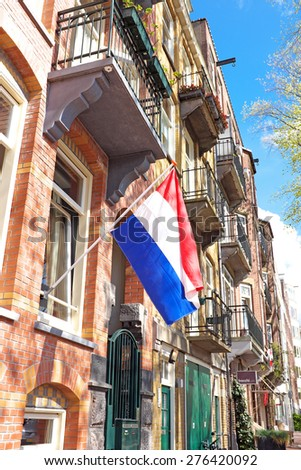 Traditional dutch house decorated with the national flag on Kings day in Amsterdam the Netherlands - stock photo