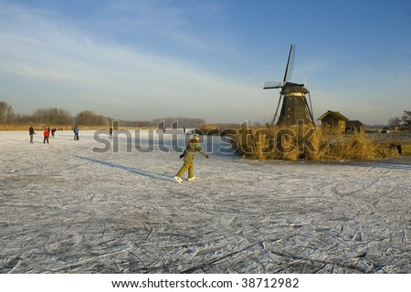 traditional dutch ice skating in the winter on a lake with a windmill - stock photo