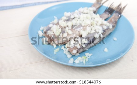 Traditional Dutch raw herring with onions on plate on wooden background