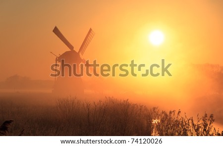 Traditional Dutch windmill at a foggy, colorful spring sunrise.