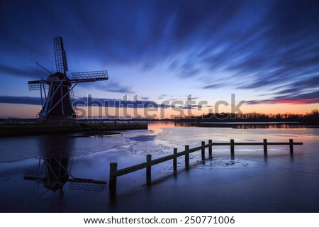 Traditional, Dutch windmill at a lake just after a nice sunset in winter. Long exposure. - stock photo