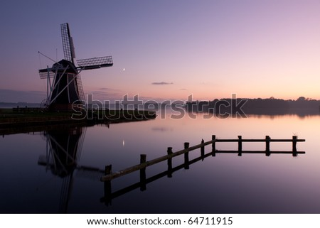 Traditional Dutch windmill at dusk, with the new moon and a star in the sky. - stock photo