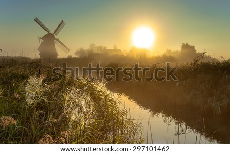 Traditional dutch Windmill in a marshland area with cobwebs in reed on a foggy morning in september