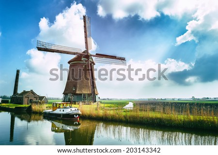 Traditional dutch windmill near the canal. Netherlands - stock photo