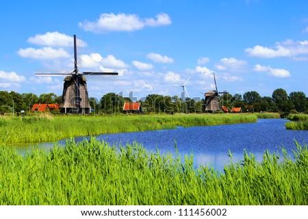 Traditional Dutch windmills along a canal near Alkmaar, Netherlands - stock photo