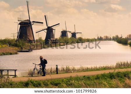 Traditional Dutch windmills and tourist by bike - stock photo