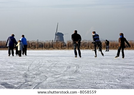 Traditional dutch winter image, ice skating in the fields from Holland - stock photo