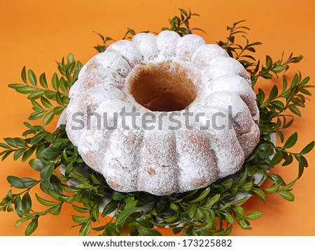 Traditional Easter Cake sprinkled with powdered sugar over orange background - stock photo
