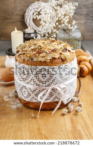 Traditional easter cake with icing and raisins decorated with white lace and ribbon - stock photo