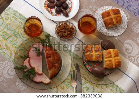 Traditional easter dinner set with sliced meat, bread with herbs, handmade colored eggs, chocolates, easter cake and glasses of juice on colorful tablecloth, horizontal top view - stock photo