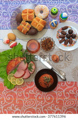 Traditional easter dinner set with sliced meat with lemon and herbs, bread, handmade colored eggs, chocolates, raisins, easter cake and glasses of juice on colorful tablecloth, top view - stock photo