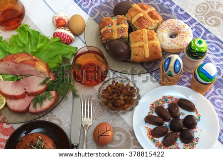 Traditional easter dinner set with sliced meat with lemon and herbs, bread, handmade colored eggs, chocolates, raisins, easter cake and glasses of juice on colorful tablecloth, horizontal top view - stock photo