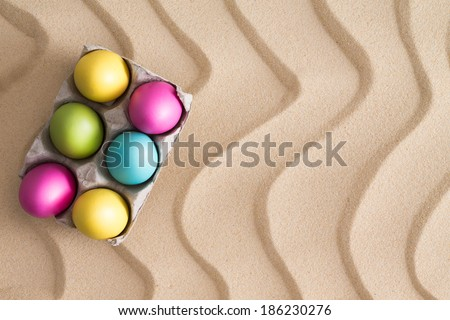 Traditional Easter Egg hunt at the beach with a box of colorful painted eggs hidden on golden sand with a decorative wavy pattern and copy space for your seasonal greeting - stock photo