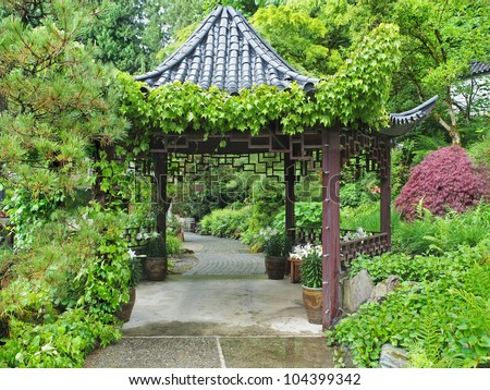 Traditional Eastern  gazebo frames the pathway in the lush garden - stock photo