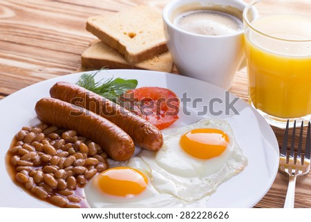 Traditional English breakfast with sausage, fried eggs, beans, coffee and orange juice