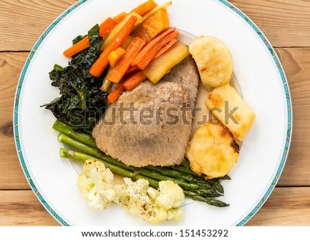 Traditional english british sunday lunch of roast beef, roasted potatoes, carrots, parsnips,kale,cauliflower on china plate - stock photo