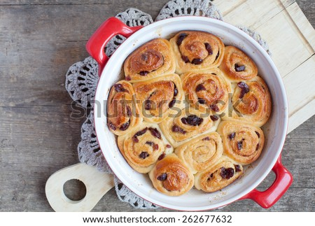 Traditional English buns Chelsea with dried cranberries and cinnamon on wooden table, selective focus and space for text - stock photo