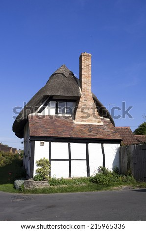 traditional english cottage with half timbered beams and a thatched roof - stock photo