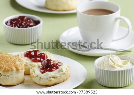 Traditional English cream tea of scones, clotted cream, strawberry jam and a cup of tea. These are served Devonshire style, with the jam on top. - stock photo