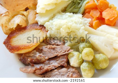 Traditional English sunday roast lamb dinner with yorkshire pudding and fresh garden vegetables, macro