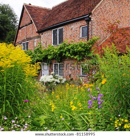 Traditional English Village Cottage full of colorful Summer Flowers - stock photo