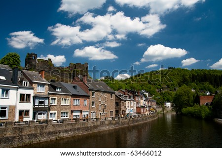 Traditional european houses in Ardennes on a bank of a river - stock photo