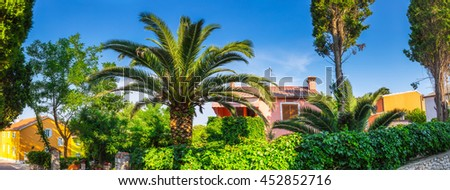 Traditional european Mediterranean architectural style the streets and residential houses, yellow, pink, orange building in the afternoon light, surrounded by greenery cypress and palm trees in summer - stock photo