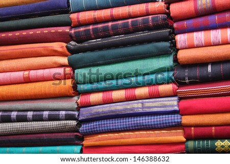 Traditional fabric store with stacks of colorful textiles.